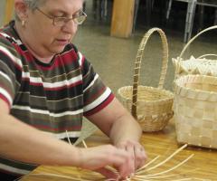 Une femme fabrique un panier